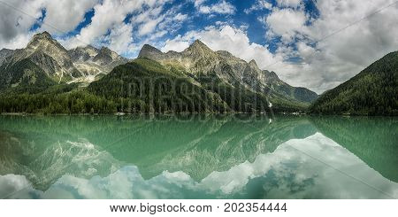 Lake of Anterselva surrounded by mountains with blue sky and clouds in the background on a summer day Sud Tirol Italy