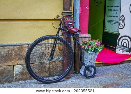Krakow/Poland- August 15, 2017: Retro style bicycle and basket with colorful artificial flowers decorating shop entry, Florianska street, old town
