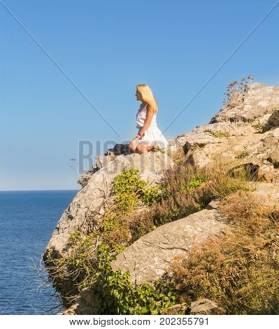 Yalta, Crimea - 11 July, A girl is posing on a precipice, 11 July, 2017. Small Castle Lastochkino Nest and its surroundings.