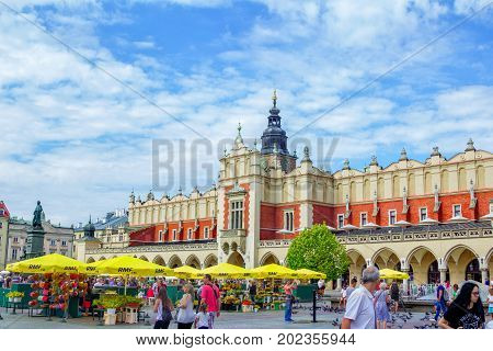 Krakow/Poland- August 15, 2017: view of main Market Square with crowds of tourists, souvenirs and flowers sellers, old Cloth Hall building, sunny summer day, blue sky