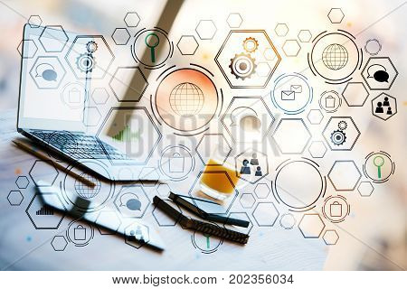 Side view of modern workplace with laptop other devices and creative business hologram. Accounting and innovation concept. Double exposure