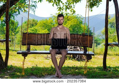 Businessman Working On A Laptop Sitting On A Swing, Working And Relaxing Outdoors.