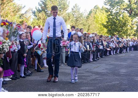 Adygea Russia - September 1 2017: student the senior class and the girl a first-grader with a bell in her hand at school the solemn ruler in day of knowledge