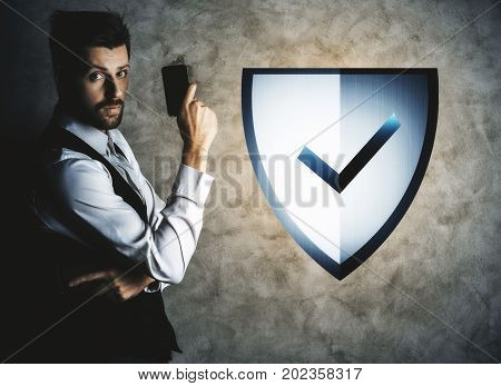 Businessman holding smartphone on concrete wall background with digital abstract antivirus shield. Guard concept