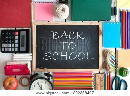 Aerial view of stationery objects with back to school on blackboard