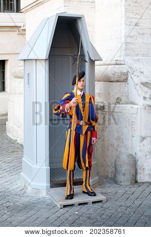 VATICAN CITY,ITALY - JULY 19, 2017 : A soldier of the Pontifical Swiss Guard standing next to Saint Peter's Square at the Vatican