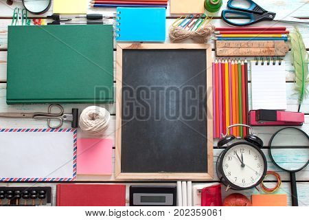 Aerial view of stationery objects with blackboard in the centre