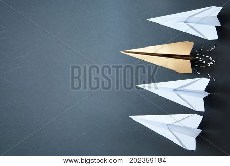 Gold paper plane standing out in a line with background space