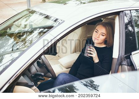 Woman resting in the car from a long journey and drinking takeaway cup of hot coffee to boost energy.