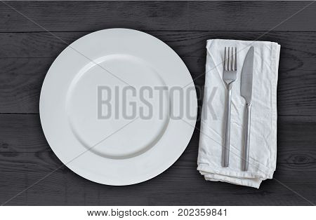 Empty plate with cutlery on anthracite wood.