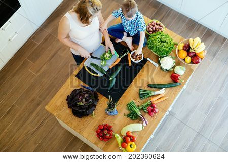 Pregnant mother and son preparing meal on kitchen counter