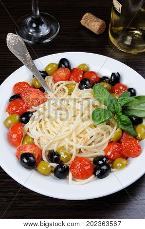 Spaghetti with olives cherry tomatoes sprinkled Parmesan and basil