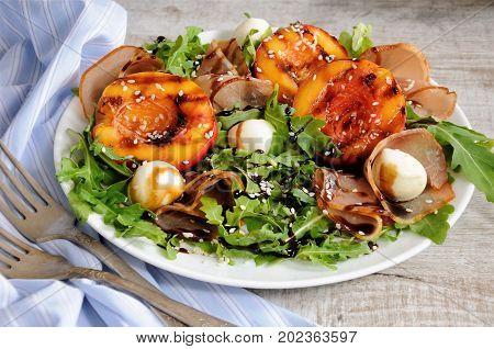 Salad with dried ham grilled nectarine mozzarella and arugula