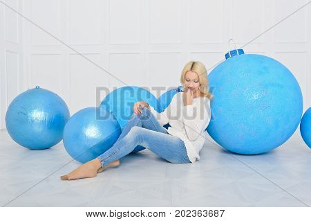 A young girl is sitting on the floor leaning on large decorative Christmas balls blue