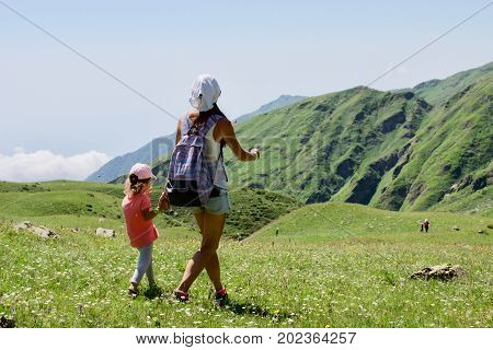 Tourist girls mother and daughter walking in mountain landscape. Family on hiking tour.