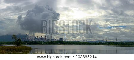 Panorama View Of Power Plant Release Steam From Stack In The Morning With Cloudy And Sun Background.