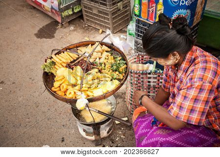 Yangon Myanmar - 2017 January 8 : A woman frying vegetables in batter and selling them on the streets of Yangon in Burma