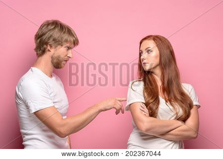 The conflict of couple - woman threatening and showing strength on pink background