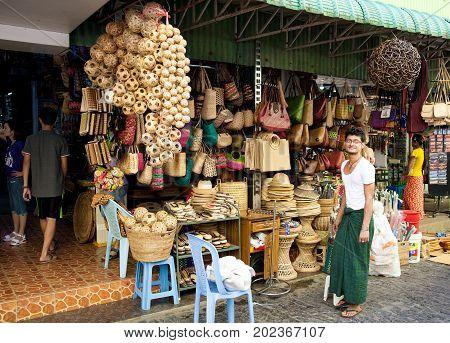 Yangon Myanmar - 2017 January 8 : A vendor of a souvenir shop selling purses hats and balls in the Bogyoke Aung San market of Yangon in Burma