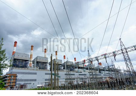 Group Of Coal Fired Power Plant And Stack With High Voltage Electricity Station And Pylon. Electrici
