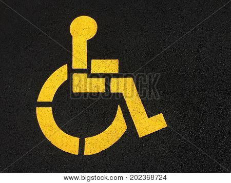 Yellow handicapped wheelchair symbol painted on black asphalt.