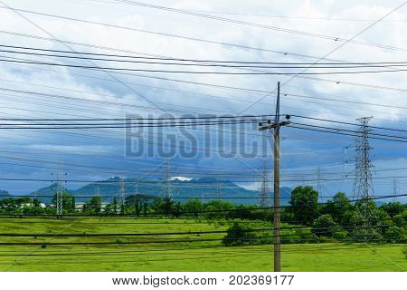 Low Voltage Pole With High Voltage Electricity Pylon And Transmission Line Background In The Filed W
