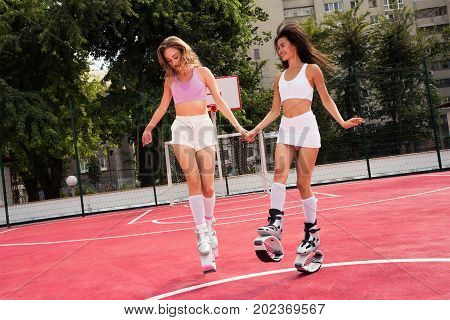 Two friends jumping and fun in kangg jumping shoes. Girls holding hands and posed in kangoo jump shoes. Happy girls on the street in special fitness shoes.
