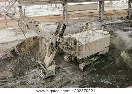 Over a big bucket excavator on a crawler track. Mining heavy industry transport. Excavator with mechanical drive and flexible suspension of work equipment.
