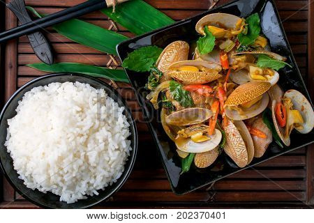 Stir fried clams with chili paste and basil leafs on wooden
