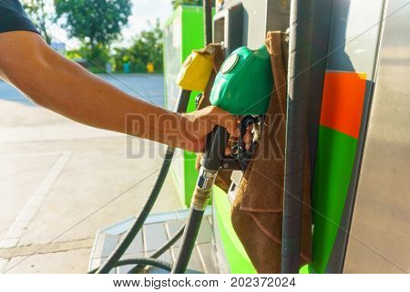 Traveller Man Hand Holding Petrol Pump Nozzle For Refueling His Car On The Road Trip In His Holiday