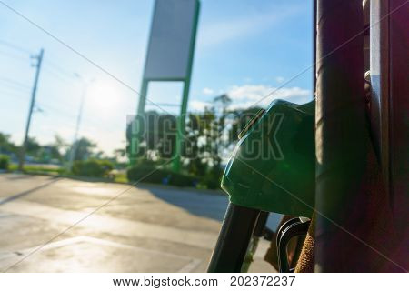 Petrol Pump Nozzle For Fill Fuel At Gas Station In Sunny Day