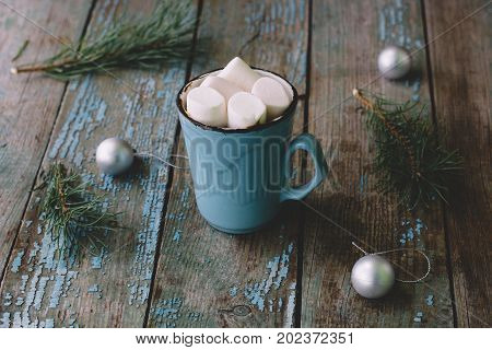 Hot Chocolate With Marshmallows In A Blue Mug On A Wooden Table Among The Spruce Branches And Christ