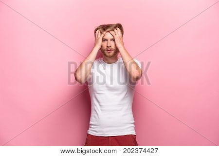 Portrait of young man with shocked facial expression at studio