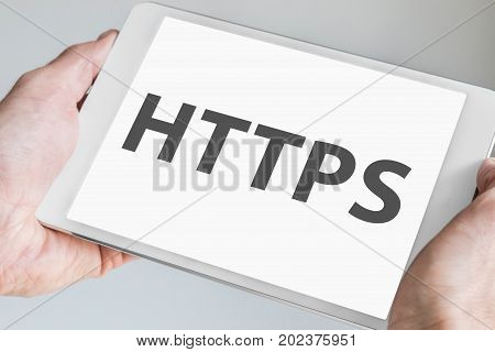 HTTPS text displayed on touch screen of a modern tablet. Hands holding mobile device to browse the internet