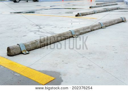 empty parking lot with cement wheel barrier divide by yellow line in gas station