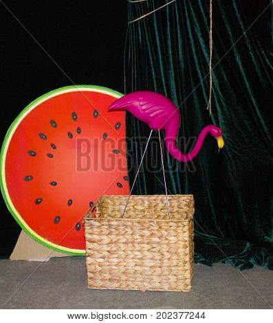 Background with a pink flamingo on a dark green background. Flamingo watermelon. woven baskets. Flamingo