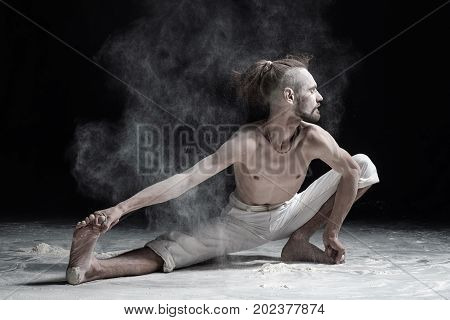Flexible yoga man doung wide side lunge or utthita namaskarasana. Dust flying in air. aghori concept