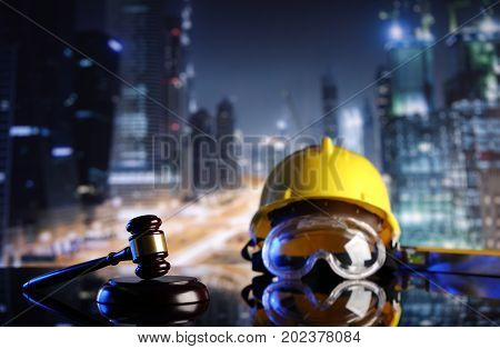 Construction law symbols. Helmet and gavel on the constuction background.