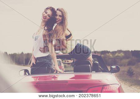 two girls having fun in cabrio tonned