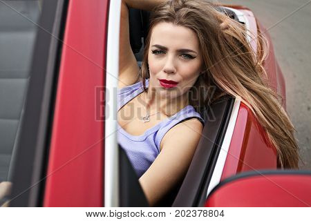 young pretty girl with red lips in red cabrio