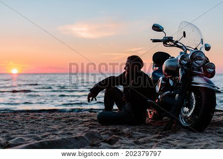 biker near motorcycle on the beach at sunset