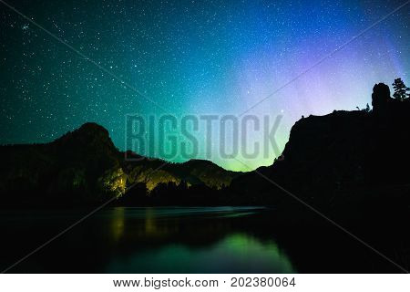 Northern Lights Over Mountains And Water