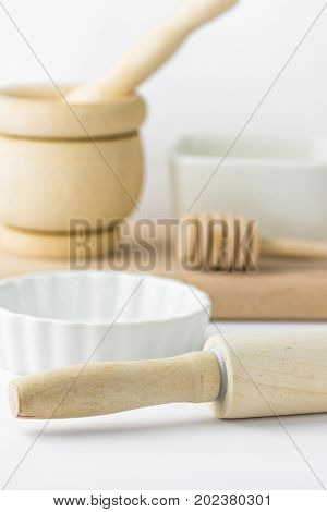 Wooden rolling pin mortar and pestle honey dipper baking form and cutting board on white tabletop. Minimalist styled image. Conceptual. Copy space for text. Banner social media poster template.