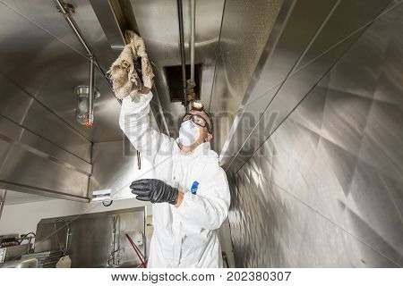 A Commercial kitchen worker washing up at sink in professional clothes