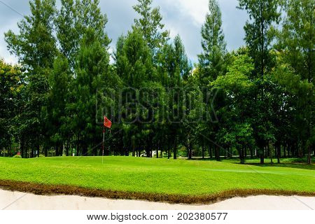 beautiful idyllic view of green with sand trap and red flag and view of forest blue sky with clouds