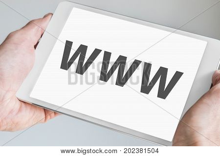 WWW (world wide web) text displayed on touch screen of modern tablet. Hands holding white mobile device