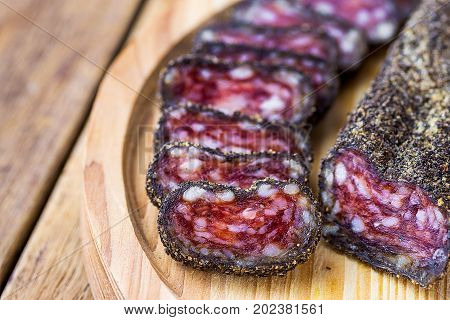 Dry-cured sausage coated with black pepper crust sliced on wood cutting board. Traditional Spanish or mediterranean delicacy. Close up copy space. Template for poster menu.