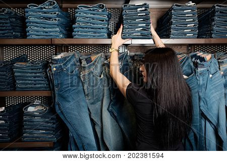 seller in jeans store shows heap of jeans