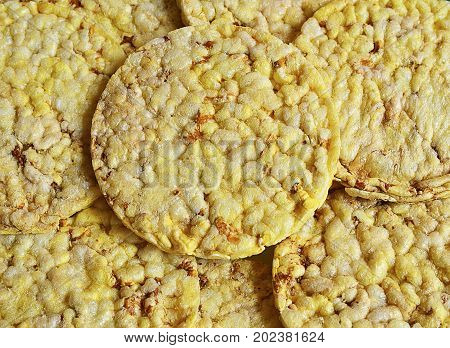Grain crispbreads close up macro as a background.Stack of puffed whole grain crispbread.Rice cake puffed rice texture.Round rice cakes background.Corn crackers. Rice galettes.Selective focus.