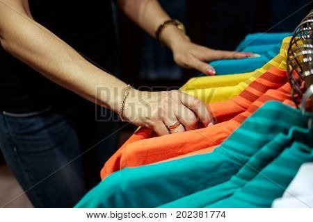 woman in clothes store choosing t-shirt hands close up